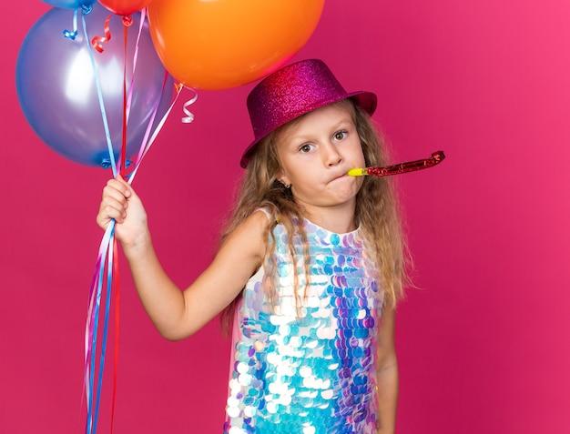 Enttäuschtes kleines blondes mädchen mit lila partyhut, der heliumballons hält und partypfeife bläst, isoliert auf rosa wand mit kopierraum