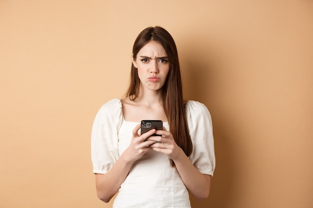 Enttäuschtes mädchen mit stirnrunzelndem smartphone, verzogenen lippen, schlechte nachrichten am telefon lesend, auf beigem hintergrund stehend.