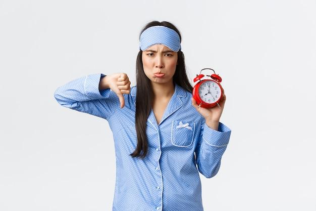 Enttäuschtes schmollen und störte süßes asiatisches mädchen im blauen pyjama und in der schlafmaske, die sich beschwerten