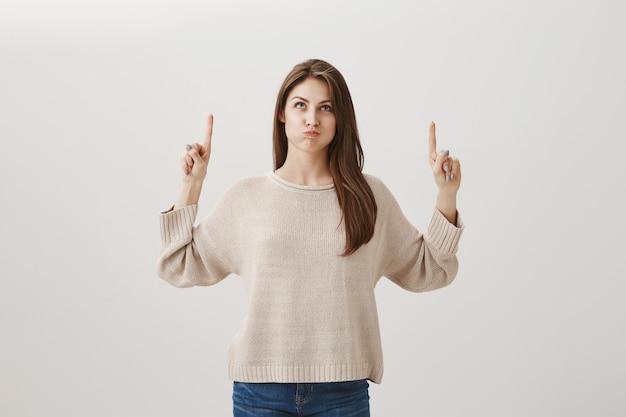 Enttäuschtes schmollendes mädchen, das mit unzufriedenem ausdruck nach oben schaut und die finger zeigt