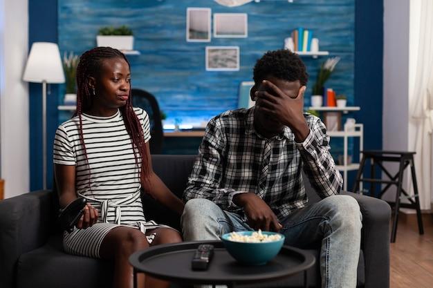 Enttäuschtes schwarzes paar verliert bei videospiel im fernsehen