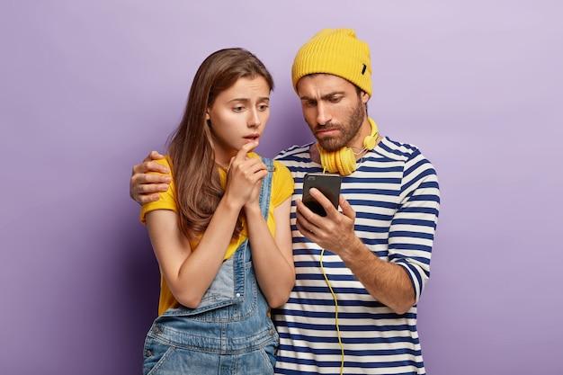 Enttäuschtes stilvolles paar, das mit smartphone aufwirft