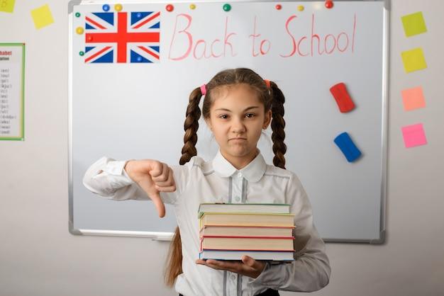 Enttäuschtes und trauriges schulmädchen, das großen finger nach unten zeigt und im klassenzimmer steht