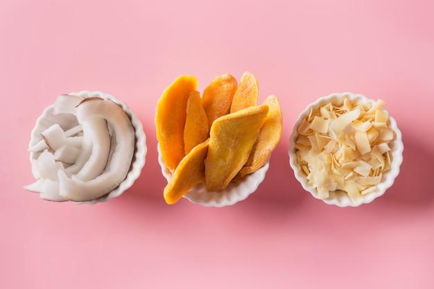Entwässerte und getrocknete mango- und kokosnusschips in der weißen schüssel auf rosa abschluss oben