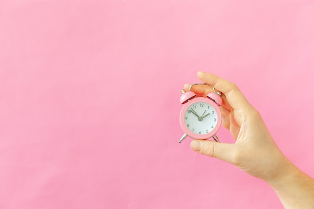 Entwerfen sie einfach die hand der weiblichen frau, die den klingelnden doppelglocken-wecker klingelt, lokalisiert auf dem bunten trendigen hintergrund des rosa pastells