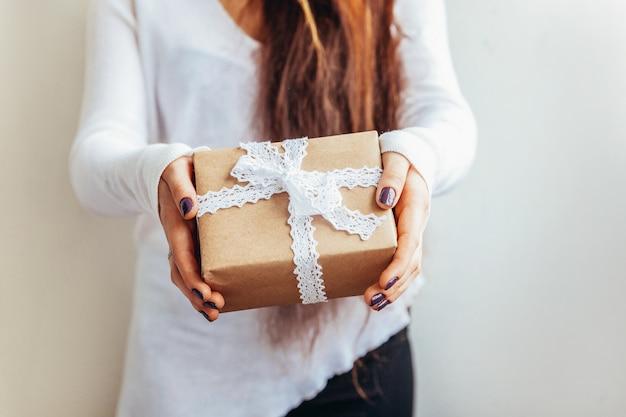 Entwerfen sie einfach die weibliche frauenhand, die braune geschenkbox der weinlese lokalisiert hält