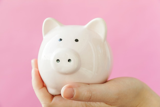 Entwerfen sie einfach die weibliche frauenhand, die das rosa sparschwein lokalisiert auf rosa buntem modischem pastell hält