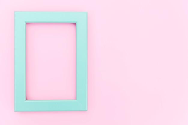 Entwerfen sie einfach mit leerem blauen rahmen, der auf buntem hintergrund des rosa pastells lokalisiert wird