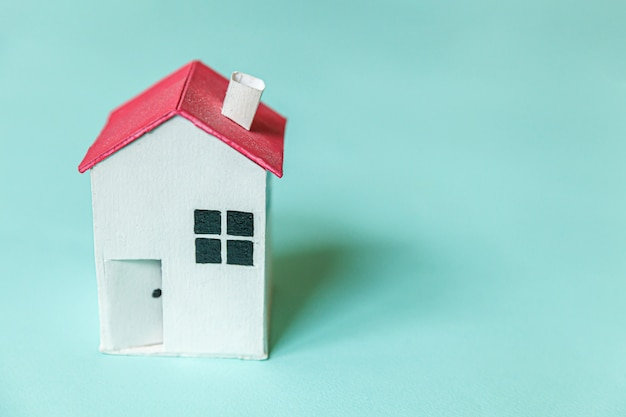 Entwerfen sie einfach mit weißem miniaturspielzeughaus lokalisiert auf bunter trendiger wand des blauen pastells. hypotheken-sachversicherungs-traumhauskonzept. kopierraum für flache draufsicht.