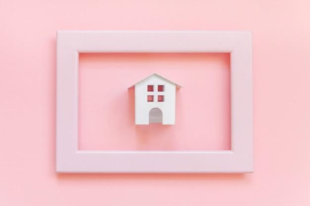 Entwerfen sie einfach mit weißem spielzeugminiaturhaus im rosa lokalisierten rahmen