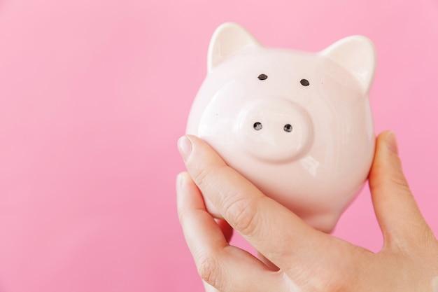 Entwerfen sie einfach weibliche frauenhand, die rosa sparschwein lokalisiert auf rosa pastellbuntem trendigem hintergrund hält