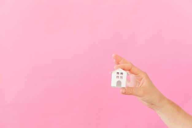 Entwerfen sie einfach weibliche hand der frau, die weißes miniaturspielzeughaus der miniatur lokalisiert auf buntem trendigem hintergrund des rosa pastells hält