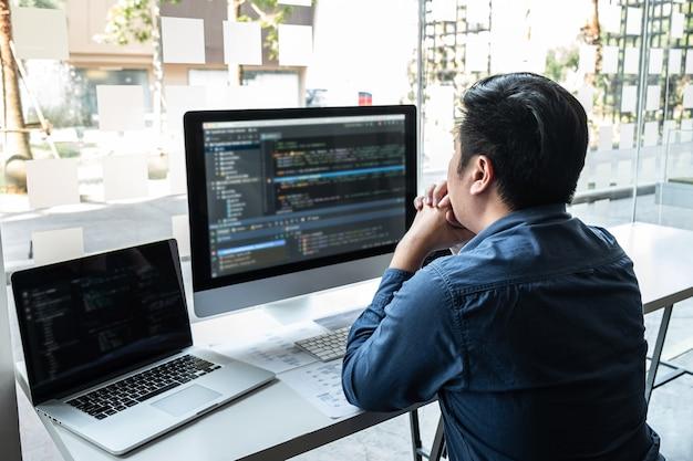 Entwicklerprogrammierer, der an einem projekt im softwareentwicklungscomputer im it-unternehmensbüro arbeitet, codes und datencode-websites schreibt und datenbanktechnologien codiert, um eine lösung für das problem zu finden.
