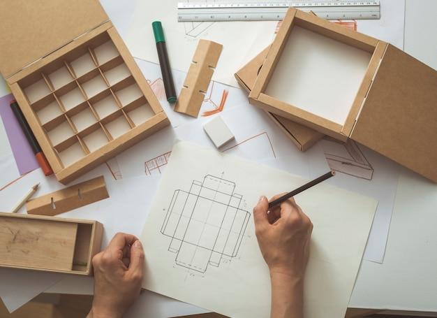 Entwicklung konstruktionszeichnung verpackung. desktop einer kreativen person, die pappschachteln herstellt.