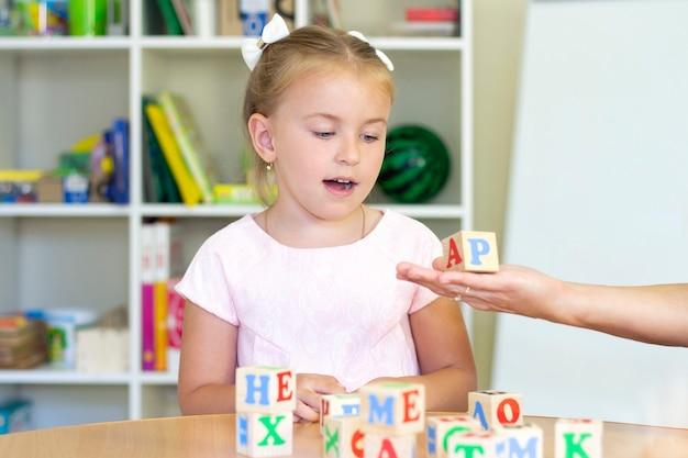 Entwicklungs- und sprachtherapiekurse mit einem mädchen. sprachtherapieübungen und spiele mit buchstaben.