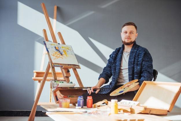 Entworfen vom künstlermann, der sein meisterwerk beendet, hält einen pinsel in der hand.