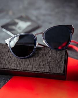 Entworfene sonnenbrille auf dem roten buch und der grauen oberfläche