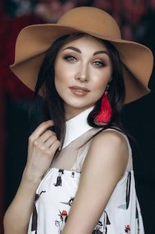 Entzückende lächelnde Frau im beige Hut und mit Modeblick wirft im Studio auf