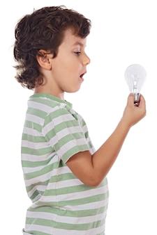 Entzückender Junge, der eine Glühlampe über weißem Hintergrund hält