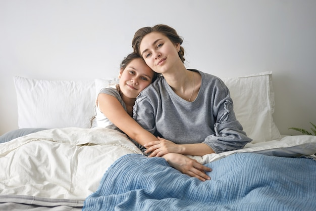 Entzückend süßes weibliches kind, das im bett sitzt und ihre attraktive mutter umarmt.