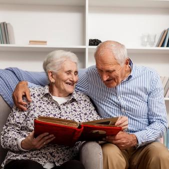 Entzückende ältere paare, die fotoalbum untersuchen