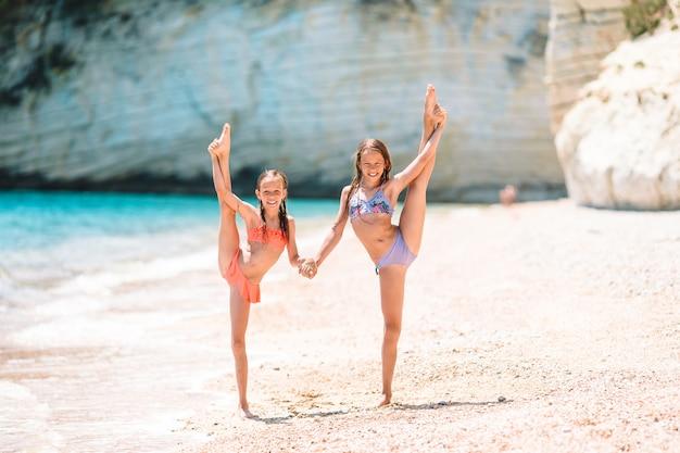 Entzückende aktive kleine mädchen am strand während der sommerferien