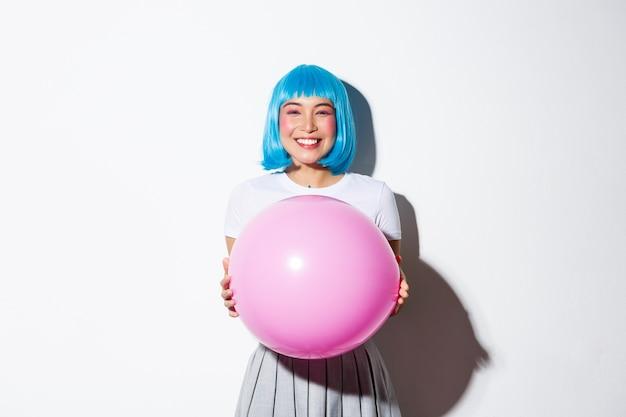 Entzückende asiatische frau, die feiertag feiert, ballon hält und blaue perücke für halloween, stehend trägt.