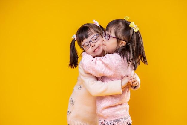 Entzückende außergewöhnliche kinder. charmante positive schwestern mit chromosomenanomalien, die sich umarmen und äußerst liebenswert sind
