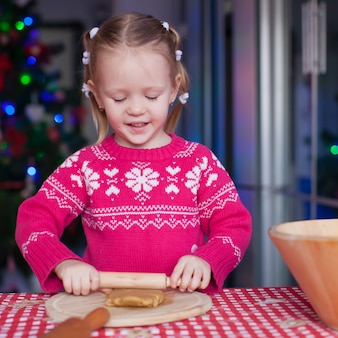 Entzückende backenlebkuchenplätzchen des kleinen mädchens für weihnachten