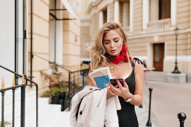 Entzückende blonde frau, die nachricht am telefon schreibt, das in der mitte der straße steht