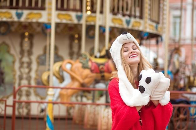 Entzückende blonde frau mit rotem strickpullover und lustigem hut, die im hintergrund des karussells mit lichtern posiert