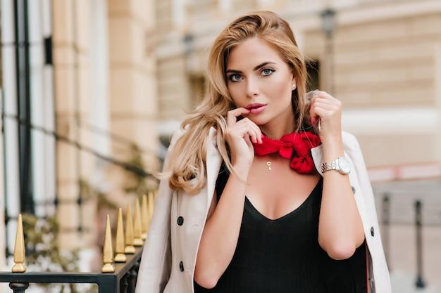 Entzückende blondhaarige frau, die niedlichen anhänger trägt, der vor gebäude steht, eingewickelt in mantel