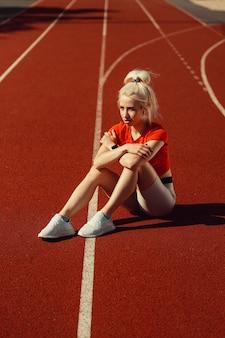 Entzückende blondine sitzt auf einer joggingstrecke
