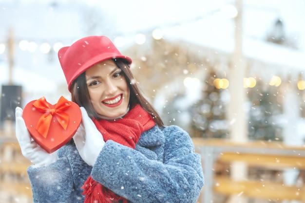 Entzückende brünette frau im wintermantel, die während des schneefalls eine geschenkbox auf dem weihnachtsmarkt hält platz für text