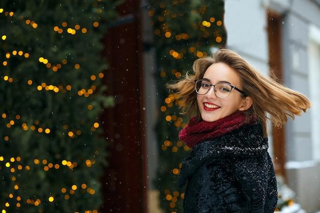 Entzückende brünette frau mit schal und brille, die schneefälle genießt. freiraum