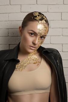 Entzückende brünette junge frau mit goldener folie auf gesicht, haar und hals