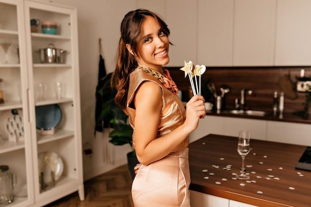 Entzückende charmante dame, die glanzoutfit trägt, das mit champagner und festlichen requisiten aufwirft.