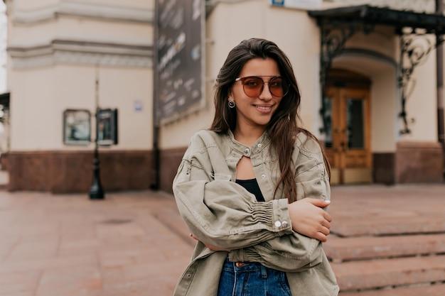 Entzückende dame mit dem langen dunklen haar, das jeansjacke trägt, die über alten gebäuden im stadtzentrum aufwirft