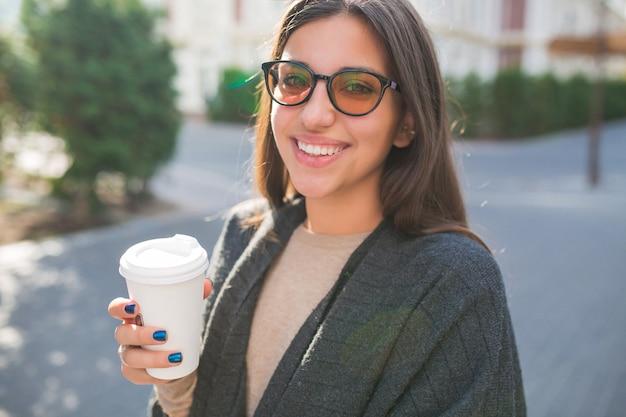 Entzückende dame mit einer tasse kaffee, die draußen im sonnigen guten tag auf stadtplatz geht