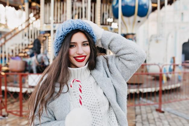 Entzückende dunkelhaarige frau, die freizeit im vergnügungspark am winterwochenende verbringt. foto im freien der atemberaubenden brünetten dame im blauen hut, der weihnachtsbonbons nahe karussell isst.