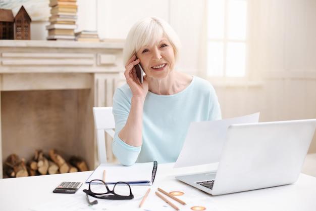 Entzückende elegante ältere frau, die mit ihrem kollegen am telefon spricht, während sie am tisch sitzt und ihren laptop benutzt