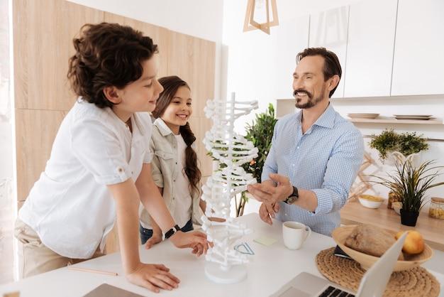 Entzückende eng verbundene familie, die um ein großes weißes 3d-dna-modell herumsteht und es von verschiedenen seiten untersucht, wobei sein vater eines der nukleotide berührt