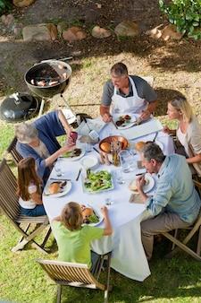 Entzückende familie, die im garten isst