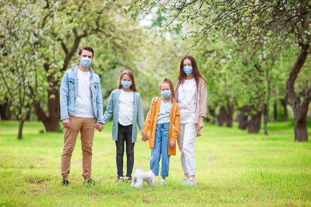 Entzückende familie im blühenden kirschgarten in masken