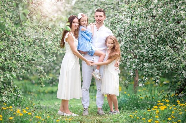 Entzückende familie in blühendem kirschgarten am schönen frühlingstag