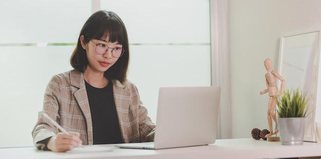 Entzückende frau, die an ihrem projekt bei der anwendung des laptops arbeitet