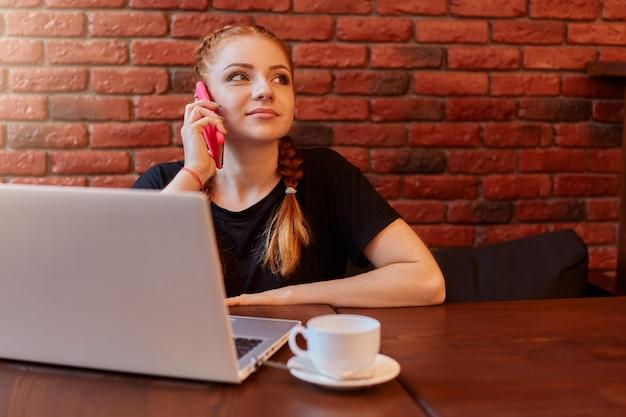 Entzückende frau, die auf smartphone im café spricht, während sie online über laptop arbeitet