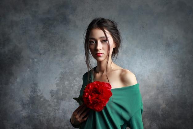 Entzückende frau, die elegantes kleid trägt, das eine rote pfingstrosenblume hält
