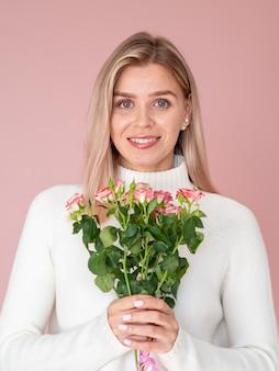Entzückende frau, die mittleren schuss der rosen hält