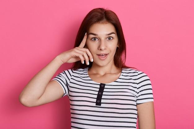 Entzückende frau hält zeigefinger an der schläfe, versucht sich mit gedanken zu sammeln, gekleidet in lässig gestreiftem t-shirt, isoliert über rosenwand, hat idee, sieht aufgeregt aus.